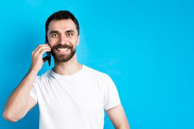 Mens die en smartphone glimlacht houdt aan oor