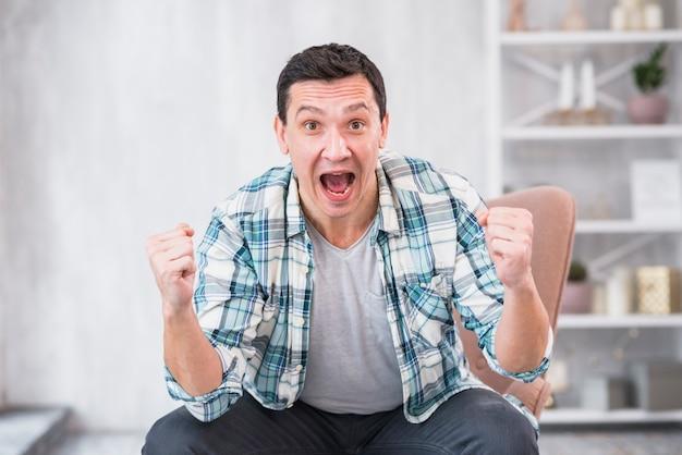 Mens die en vuisten op stoel thuis schreeuwt toont
