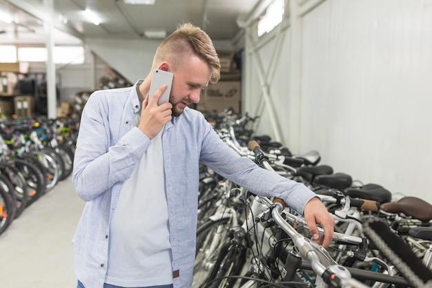 Mens die fiets bekijken terwijl het spreken op cellphone in winkel