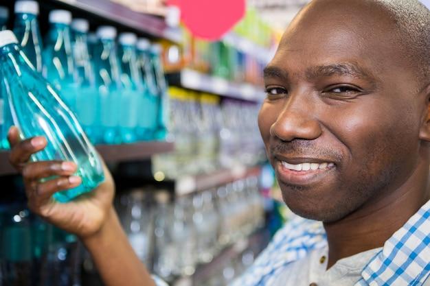 Mens die fles water in supermarkt bekijkt
