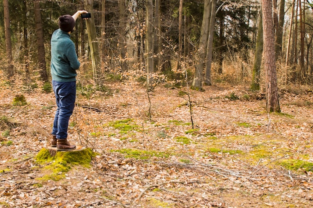 Mens die foto met smartphone in het bos neemt