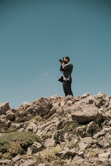 Mens die foto's op een rotsachtige berg neemt