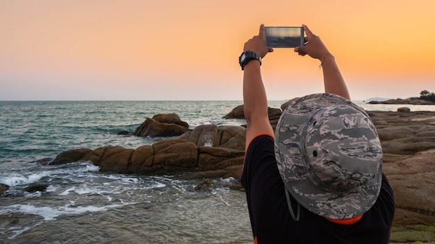 Mens die foto's van zonsondergang met mobiele telefoon neemt