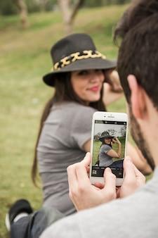 Mens die foto van haar meisje van celtelefoon neemt in het park
