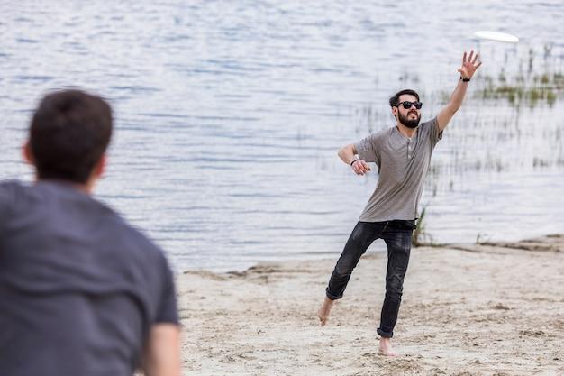 Mens die frisbee vangen die van vriend op strand vliegen