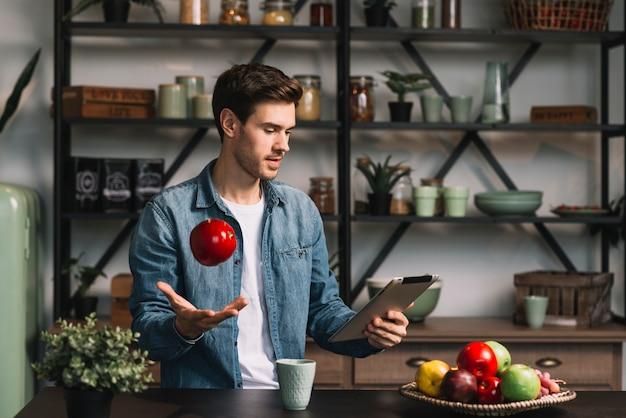 Mens die fruit in lucht werpt die digitale tablet bekijkt