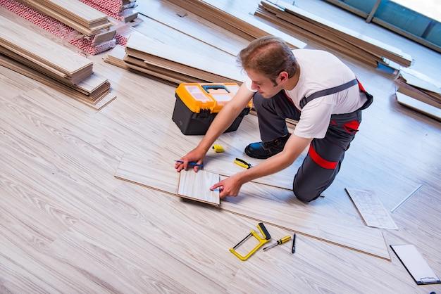 Mens die gelamineerde bevloering in bouw legt