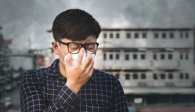 Mens die gezichtsmasker wegens luchtvervuiling draagt in de stad