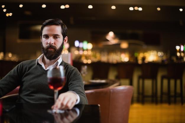 Mens die glas rode wijn bekijkt