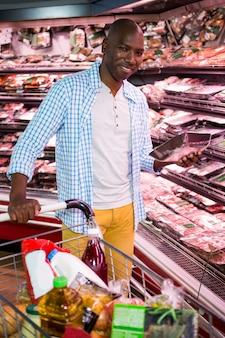 Mens die goederen in kruidenierswinkelsectie bekijken terwijl het winkelen in supermarkt