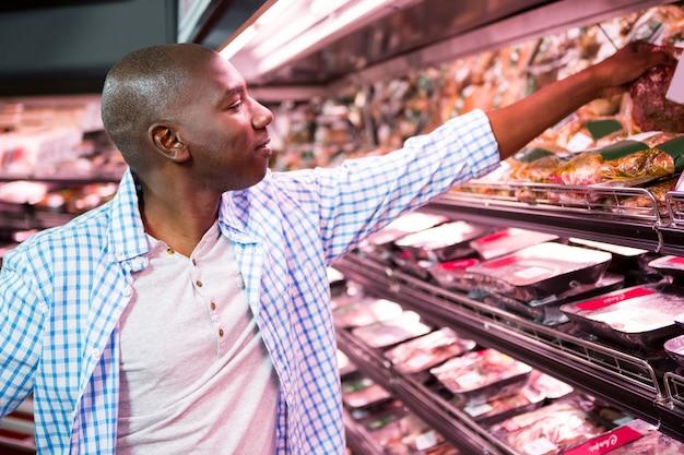 Mens die goederen in kruidenierswinkelsectie bekijken terwijl het winkelen