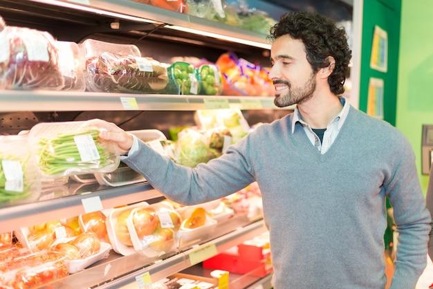 Mens die groenten in een kruidenierswinkelopslag opneemt