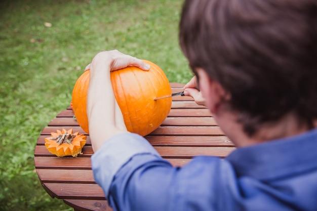 Mens die grote pompoen op een houten lijst snijdt voor halloween