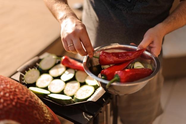 Mens die grote spaanse pepers zet aan de aubergines op de grill
