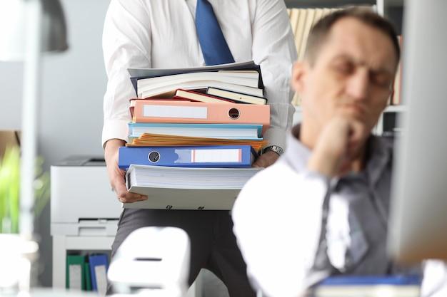 Mens die grote stapel documenten draagt aan ongelukkige collega