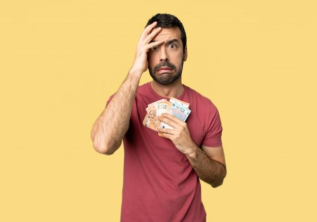 Mens die heel wat geld met verrassing en geschokte gelaatsuitdrukking op geïsoleerdee gele achtergrond neemt