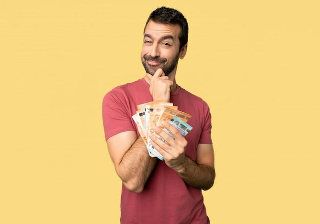Mens die heel wat geld neemt dat en aan de voorzijde met zeker gezicht op geïsoleerdee gele achtergrond glimlacht kijkt