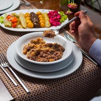 Mens die heerlijke oosterse erwtensoep met vlees op een houten lijst eet. hoge hoekmening.