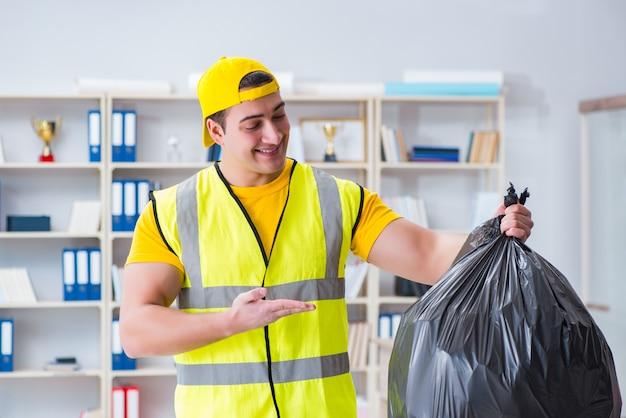 Mens die het bureau schoonmaakt en vuilniszak houdt
