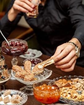 Mens die het dessert van de notenchocolade met binnen jam nemen