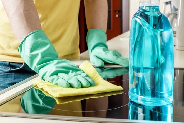 Mens die het kooktoestel in de keuken schoonmaakt