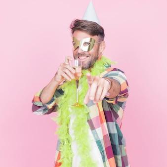 Mens die het masker van het verjaardagsoog en van de hoedenholding champagne fluit dragen die vinger naar camera richten