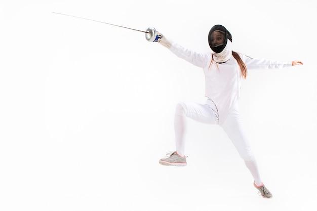Mens die het schermende kostuum oefenen met zwaard tegen grijs draagt