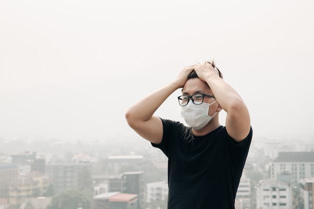 Mens die hygiënemasker en ziek wegens luchtvervuiling in de stad draagt.