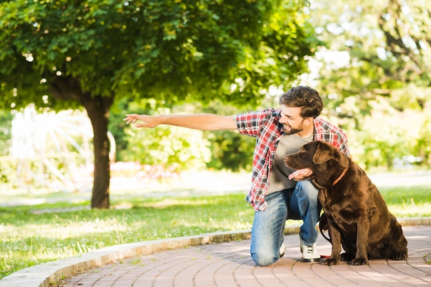 Mens die iets toont aan zijn hond in park