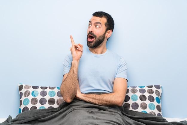 Mens die in bed een idee denkt dat de vinger benadrukt