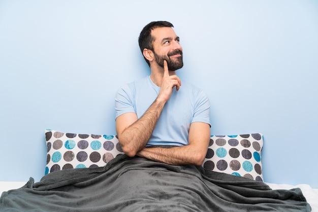 Mens die in bed een idee denkt terwijl omhoog het kijken