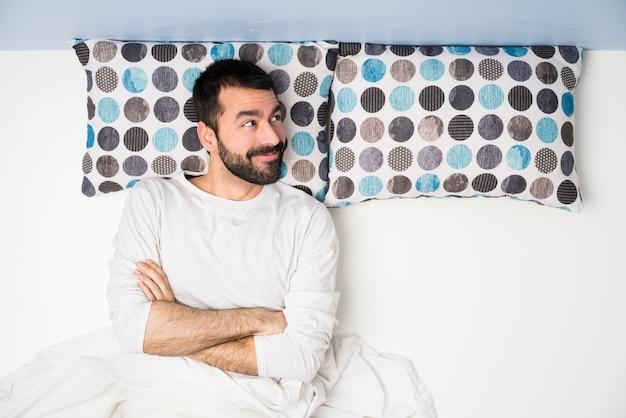 Mens die in bed in hoogste mening omhoog terwijl het glimlachen kijkt