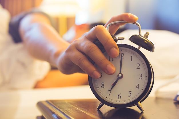 Mens die in bed ligt dat een wekker in de ochtend uitzet.