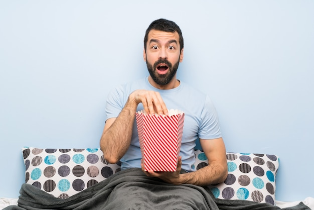Mens die in bed met baard popcorns eet