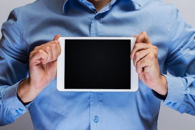 Mens die in blauw overhemd witte tabletpc houdt