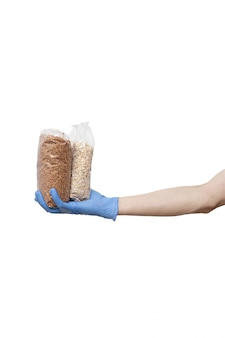 Mens die in blauwe handschoenen pakken grutten houden. zakken in de hand gehouden geïsoleerd op wit