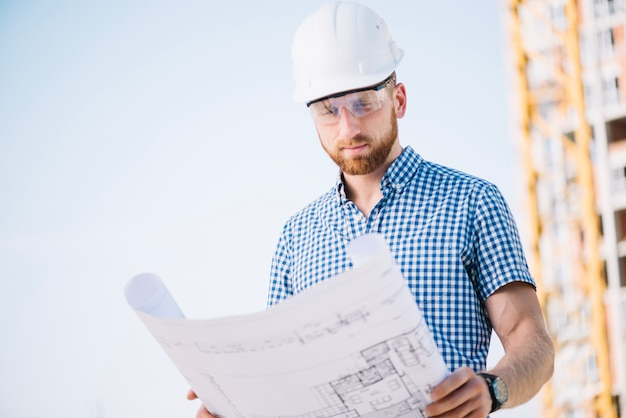Mens die in bouwvakker blauwdrukdocument bekijkt