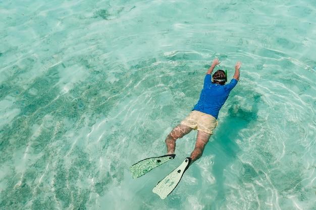 Mens die in de ongelooflijk turkooise oceaan zwemt