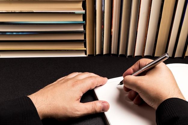 Mens die in een leeg boek naast een boekachtergrond schrijft