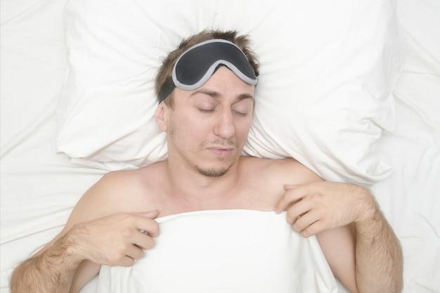 Mens die in een masker voor slaap rust. stoppels op zijn gezicht. moe man