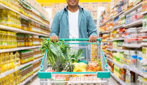 Mens die in een supermarkt, het winkelen concept winkelt
