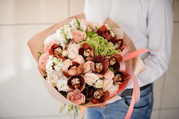 Mens die in gestreept overhemd een boeket van bloemen houdt