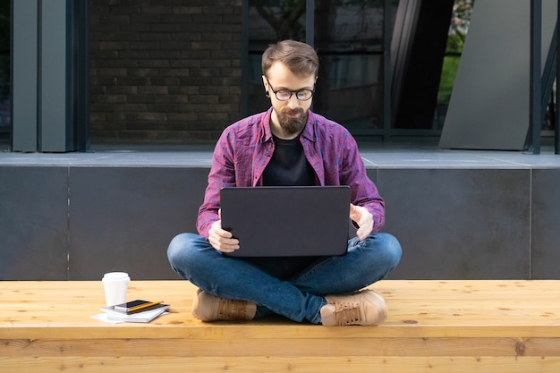 Mens die in glazen met de benen over elkaar op houten bank met laptop zitten