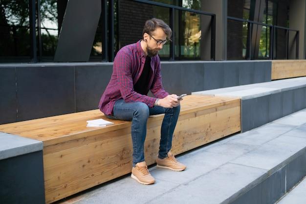 Mens die in glazen op houten bank met telefoon zitten