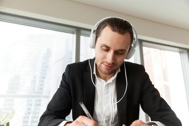 Mens die in hoofdtelefoons met pen bij het bureau schrijft