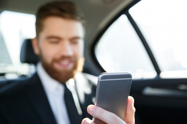 Mens die in kostuum mobiele telefoon in zijn hand bekijkt