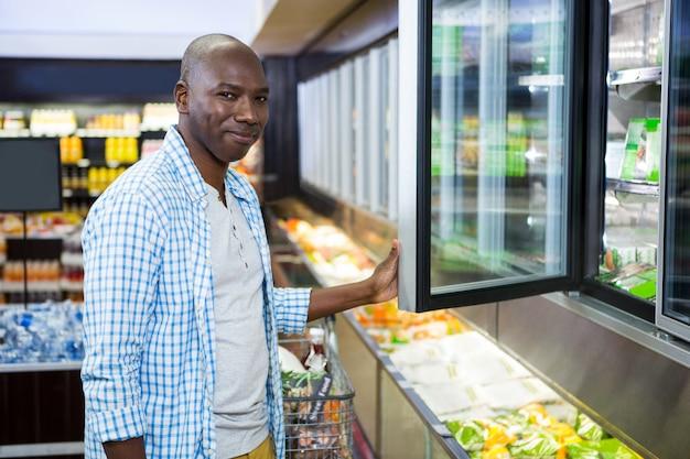 Mens die in kruidenierswinkelsectie winkelen bij supermarkt