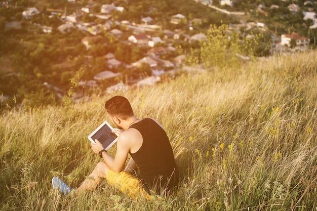 Mens die in openlucht met tabletstootkussen werkt. retro vintage instagramfilter