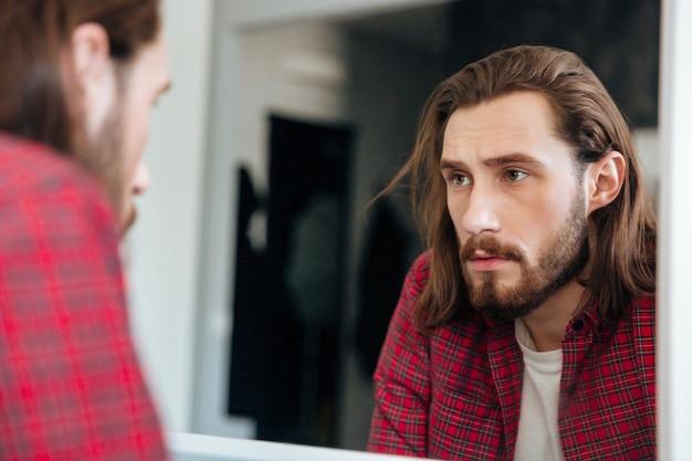 Mens die in plaidoverhemd de spiegel thuis bekijkt