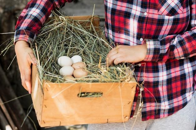 Mens die in rood geregeld overhemd een doos met een nest met eieren houdt